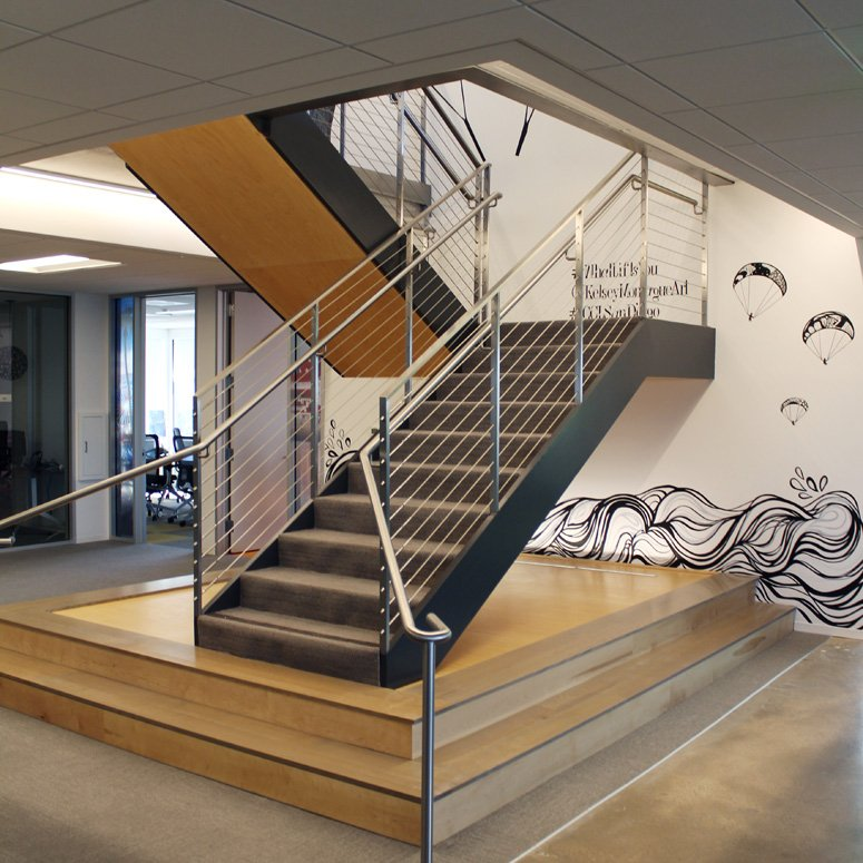 A custom mural surrounding the central staircase evokes the ocean and nearby glider port.
